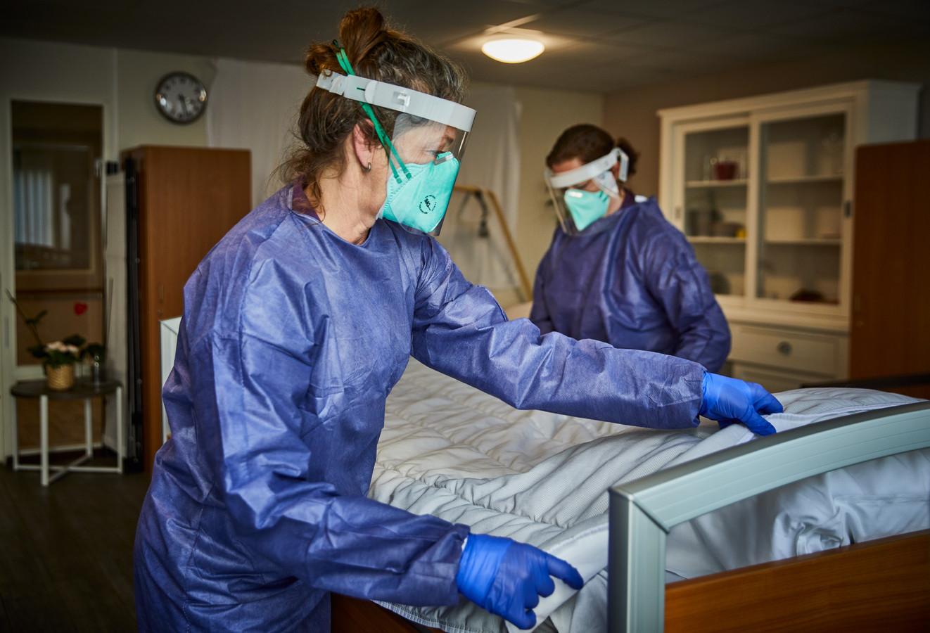 Op de speciale corona-afdeling van het verpleeghuis Aafje Smeetsland werkt iedereen urenlang met de zo kenmerkende beschermende kleding aan. Foto genomen door het raam.