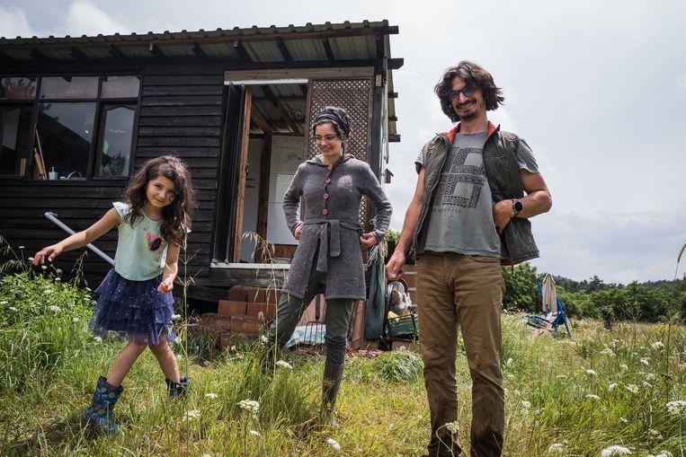 Kübra Köprülüoglu(midden) en Melih Asanli met hun dochter Asya bij hun zelfgebouwde woning in het district Bayramiç, waar ze geheel zelfvoorzienend zijn. Beeld Nicola Zolin