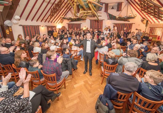 Wim Steenbakker (staand) tussen 'zijn' muzikanten en publiek op de Kerst Muziekavond in Wemeldinge.