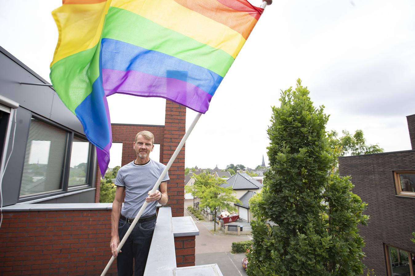 Freerk Jager, voorzitter van COC Twente-Achterhoek, hijst de regenboogvlag uit protest tegen de anti-homowetgeving in Hongarije, waar Nederland zondag de achtste finale speelt.