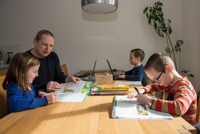Paul van Beek uit Eindhoven geeft zijn drie kinderen thuis les: Joep (bijna 10, vooraan), Niek (8) en Tessa (6).