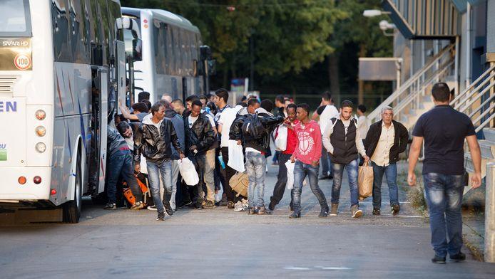 De eerste asielzoekers uit AZC Ter Apel komen aan in de Americahal, een evenementenhal en zalencentrum dat tijdelijk is omgebouwd voor de opvang van maximaal 400 vluchtelingen