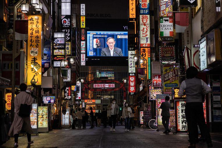 De Japanse premier Yoshihide Suga is te zien op straat tijdens de persconferentie waarin hij de noodtoestand verlengde tot 31 mei. Beeld AFP