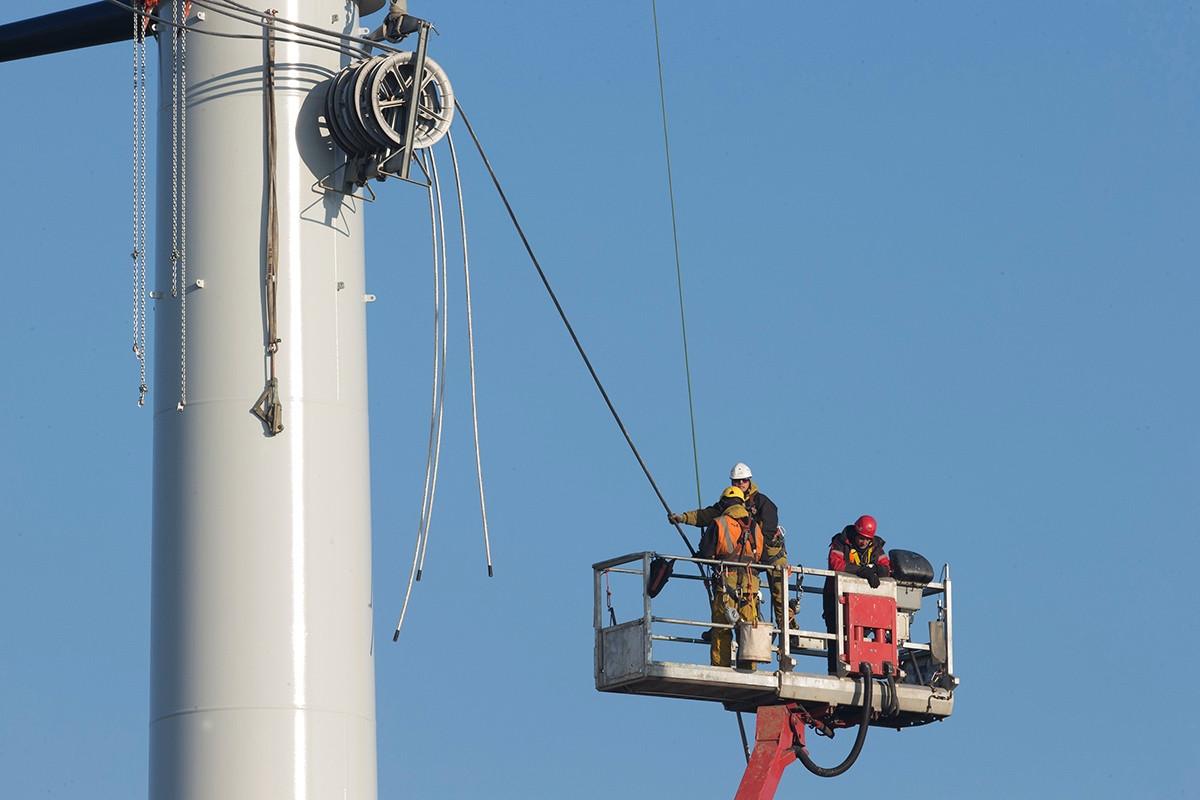 Op grote hoogte worden de kabels door de masten getrokken.