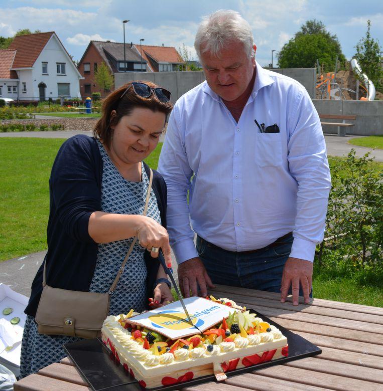 Schepen Ann Thys en burgemeester Frank Gys snijden de taart met het nieuwe logo aan