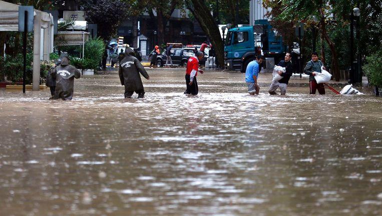 Mensen proberen een overstroomde straat over te steken in de hoofdstad Santiago. Beeld afp
