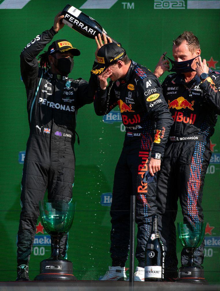 Max Verstappen wordt na zijn overwinning in Zandvoort door Lewis Hamilton met champagne overgoten.  Beeld Klaas Jan van der Weij