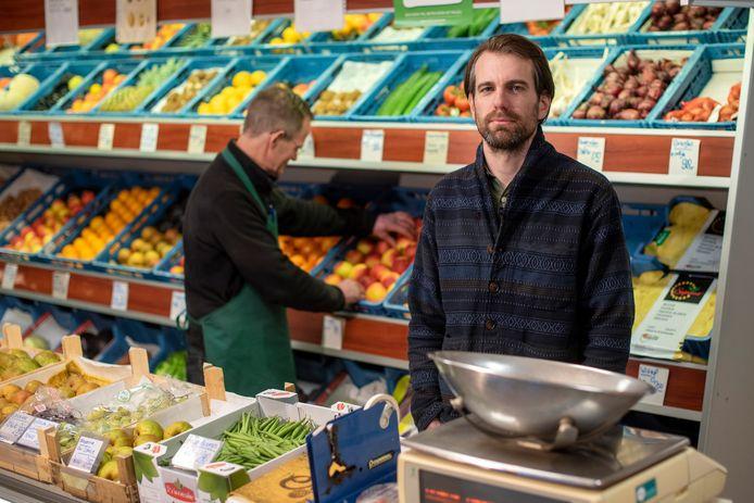 """Martijn Brugman in de zaak van zijn groenteboer Frits Mathijssen aan de Drieslag in Malburgen-Oost. ,,Dan kom ik terug met een vest van een dure winkel. Helemaal vol ben ik ervan, trots. En dan begint het. 'Pa, het lijkt wel een vloerkleed.'"""""""