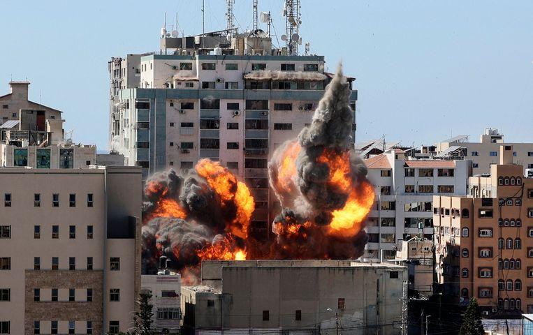 Jala Tower, waar onder meer persbureau Associated Press en nieuwszender al-Jazeera een kantoor hadden, stort in na een 'aangekondigde' raketaanval. Beeld AFP