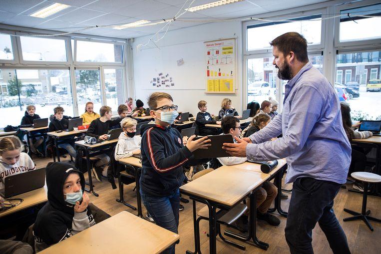 Meester Steven geeft een chromebook aan een leerling van de Katholieke basisschool Willibrordus te Oud-Beijerland  Scholen kochten in coronajaar 2020 in Nederland tenminste 45.000 Google Chromebooks met bijbehorende Google-programma's.  Beeld Arie Kievit