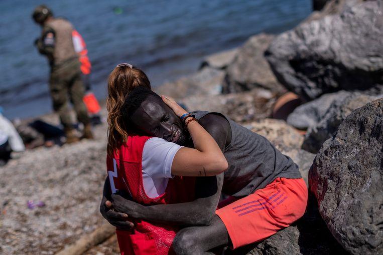 Een migrant wordt getroost door de Spaanse hulpverleners Luna Reyes. De foto brengt heel wat teweeg online, Reyes werd niet alleen overspoeld met reactise van dankbaarheid, maar ook met racistische en seksistische reacties. De migrant is ze uit het oog verloren.  Beeld AP