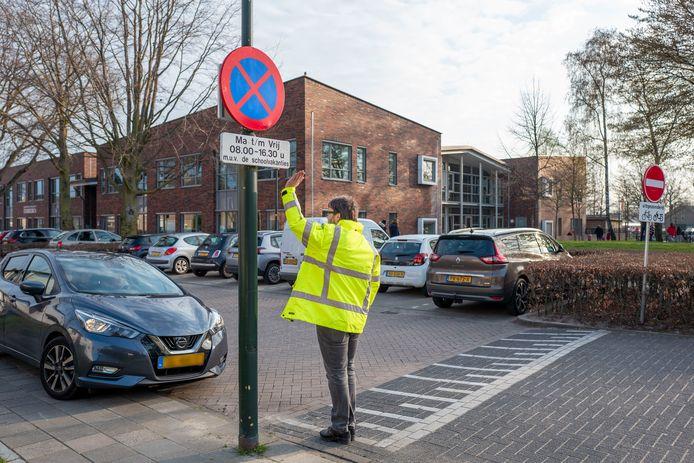 Leon van de Moosdijk wijst een moeder op het stopverbod bij basisschool Starrebos in Hilvarenbeek.
