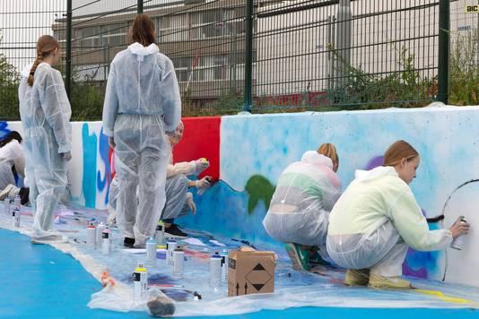 Cambium-leerlingen spuiten graffiti op de muur van het nieuw Waterplein.