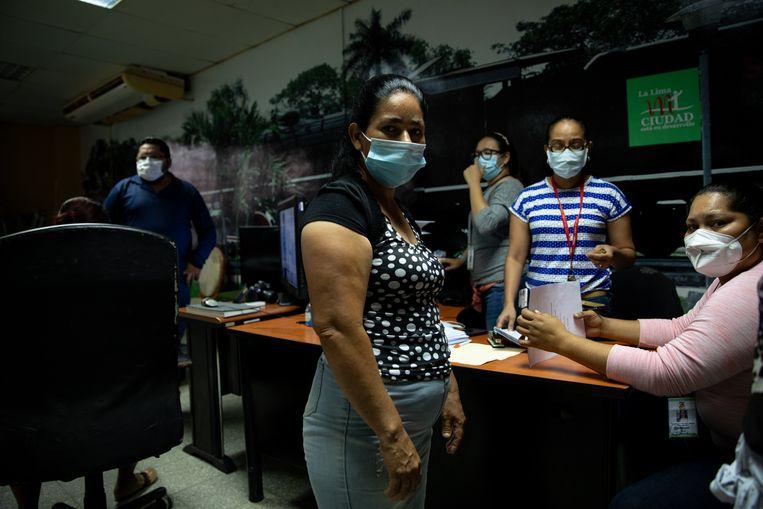 Hulpbehoevenden in de rij in het kantoor van burgemeester Santiago Motiño, die 300 lempira (10 euro) uitdeelt. Beeld Tomás Ayuso