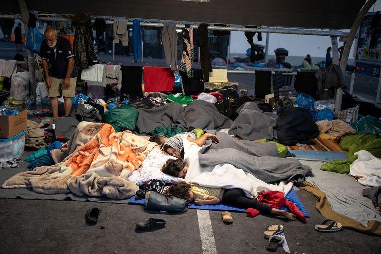 Vluchtelingen en migranten uit het vernietigde kamp Moria slapen op een supermarktparking, op Lesbos. Beeld REUTERS
