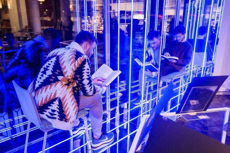 De lezende mannen in de verlichte etalage van Piet Moodshop.