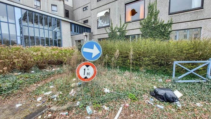 Een verloren verkeersbord, bij het ziekenhuis. Merk ook het vele zwerfvuilen de stukgegooide ruiten op