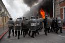 Oproerpolitie vormt een cordon om te voorkomen dat demonstranten het parlementsgebouw bestormen.