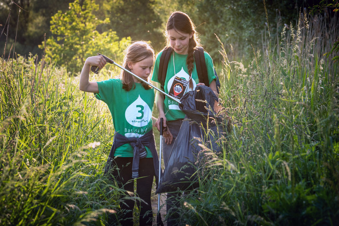 Ruby (links) en Lara verzamelen rommel in hun afvalzakken.