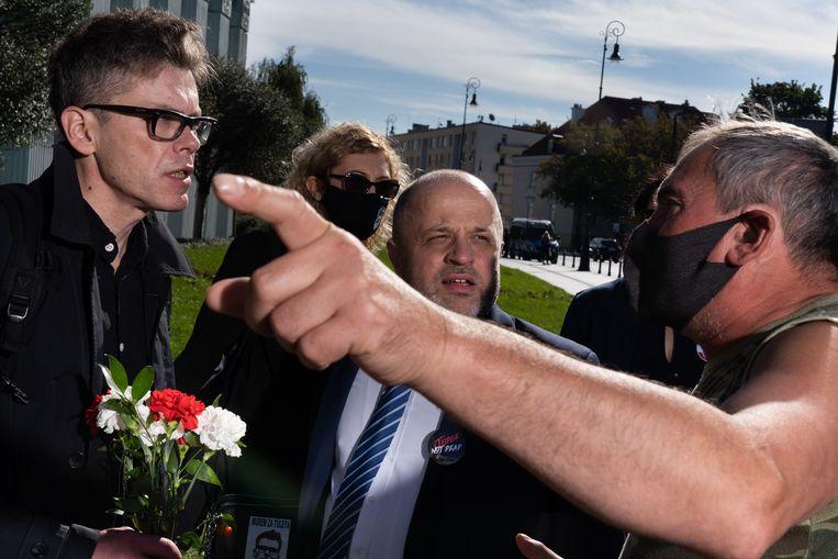 Rechter Igor Tuleya (links) eerder dit jaar in discussie met een aanhanger van de Poolse regering.  Woensdagavond heeft de tuchtkamer van de Poolse Hoge Raad Tuleya zijn onschendbaarheid ontnomen, waarmee de weg vrij is voor zijn vervolging. Beeld Piotr Malecki