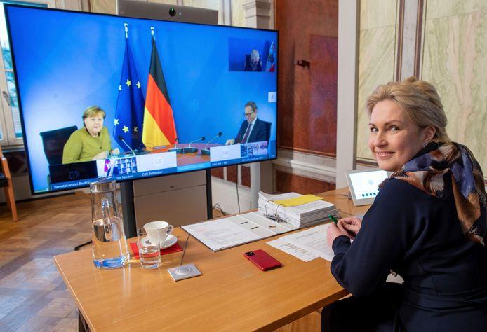 Minister-president Manuela Schwesig van de deelstaat Mecklenburg-Voor-Pommeren (voorgrond) tijdens de videoconferentie met bondskanselier Merkel (l) en Berlijns burgemeester Michael Müller die de vergadering voorzat.
