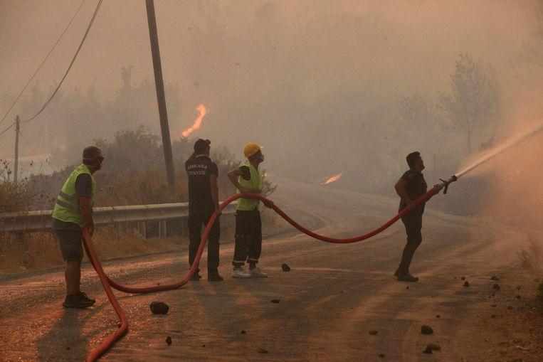 Brandweerlieden, geholpen door inwoners, blussen een brand in de Turkse kuststad Oren. Beeld AFP