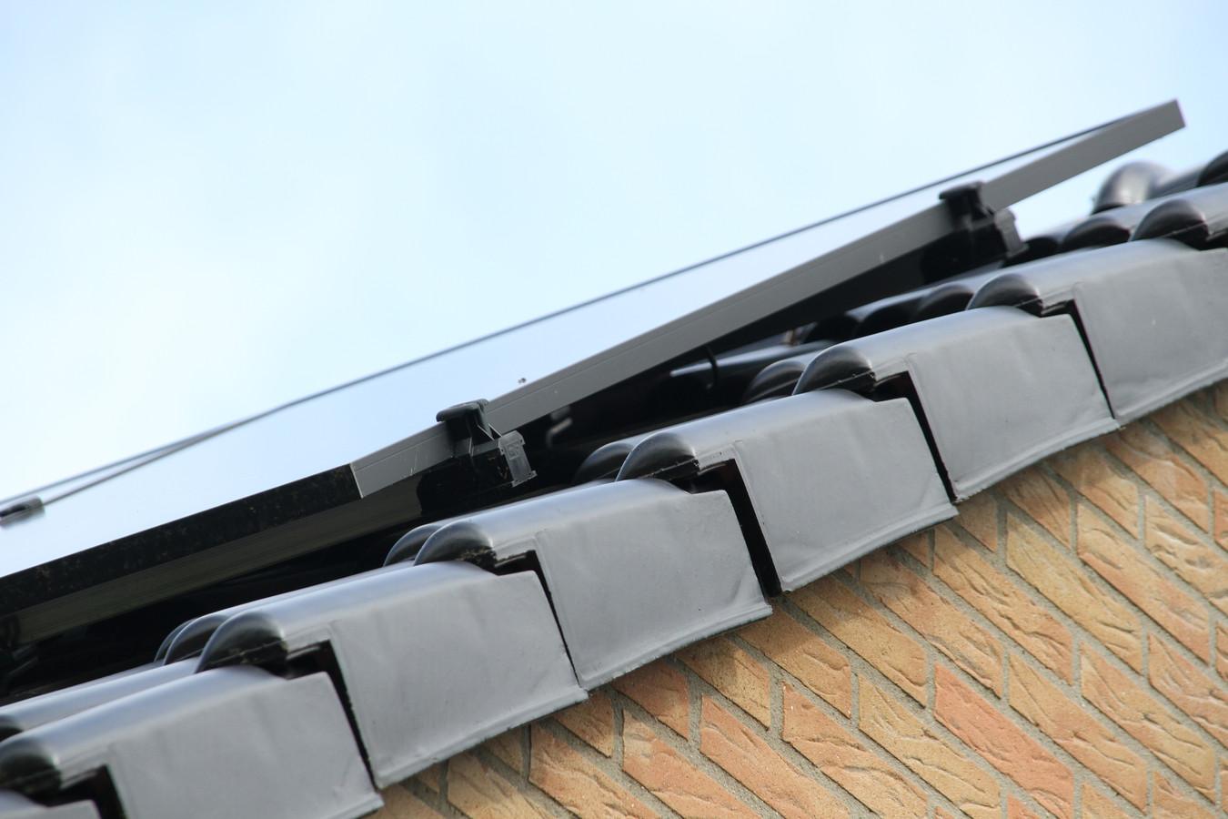 De duif zat geruime tijd vast onder de zonnepanelen op het dak.