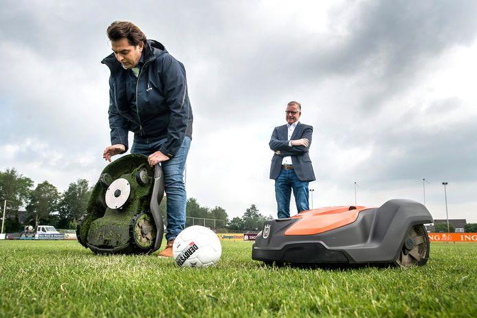 Onder het toeziend oog van wethouder René Jansen worden de robotmaaiers bij VV Dongen getoond. Achter het ronde blad zitten enkele scherpe mesjes die het gras op de millimeter nauwkeurig korten.