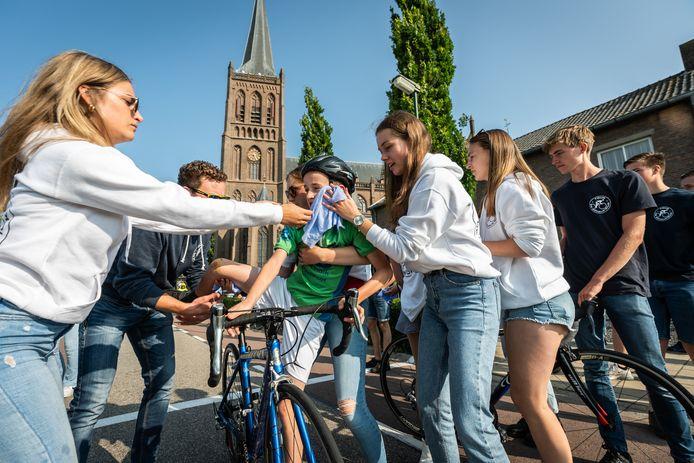 Een jonge wielrenner wordt vlak na de finish van de dinsdagse etappe Tour de Schalkwijk opgevangen door vrijwilligers.