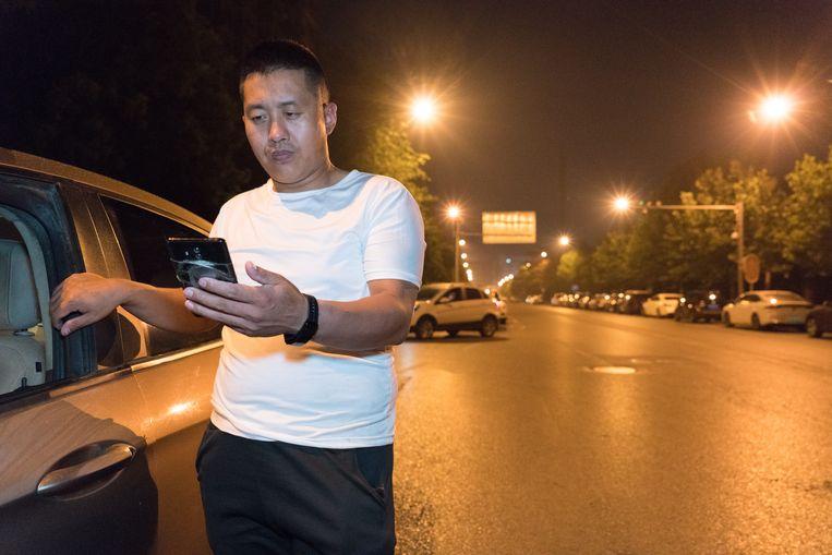 Miao Zhiwen (37) bij zijn auto om 1 uur 's nachts in Beijing. Door de nieuwe wetgeving verdient hij steeds minder.  Beeld Ruben Lundgren