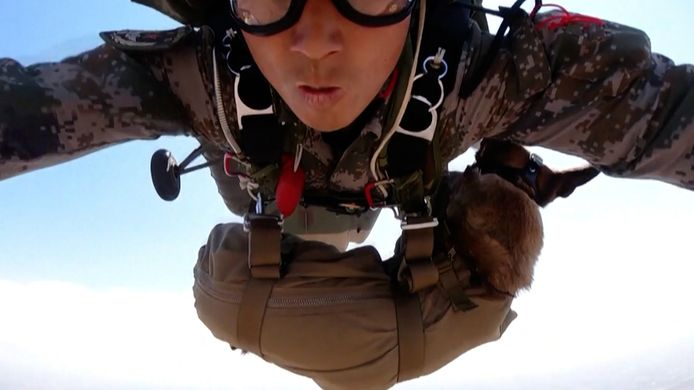 De hond Tank maakt een parachutesprong met zijn trainer Gao.