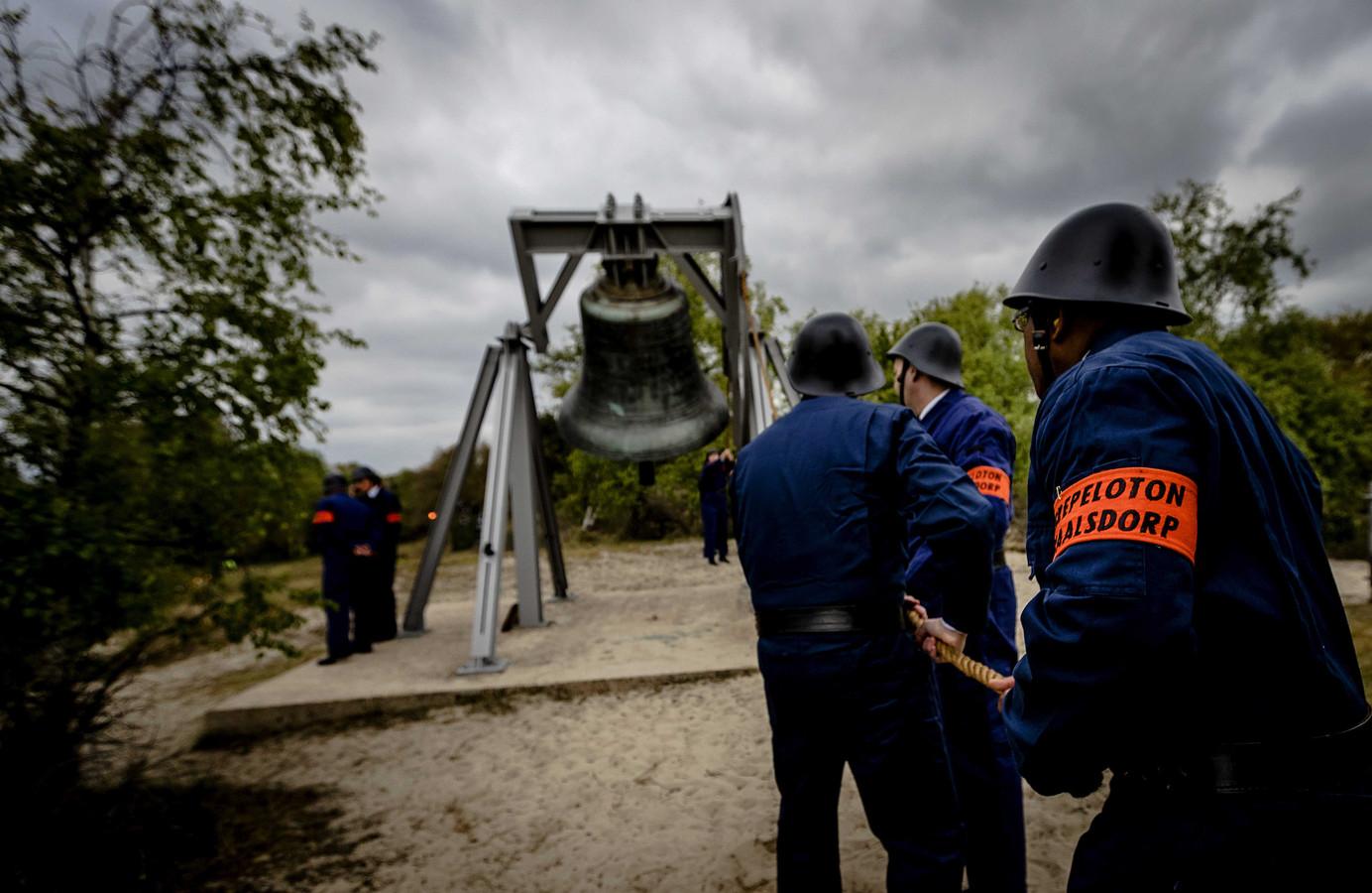 Leden van het Erepeloton Waalsdorp luiden de klok bij het monument tijdens de jaarlijkse Dodenherdenking op de Waalsdorpervlakte.