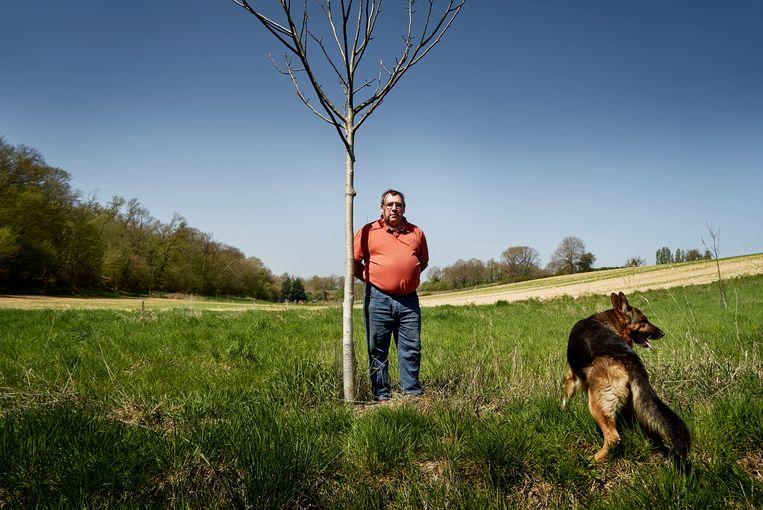 Jean-Louis Rouez, met hond Flash, legde een notenboomgaard aan. Beeld Eric de Mildt