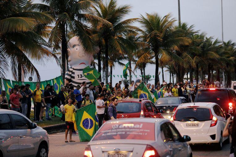 Aanhangers van de extreem-rechtse Jair Bolsonaro verzamelen zich in Rio de Janeiro bij een opblaasbare pop, 'Pixuleco', die oud-president Luiz Inacio Lula da Silva moet voorstellen.  Beeld REUTERS