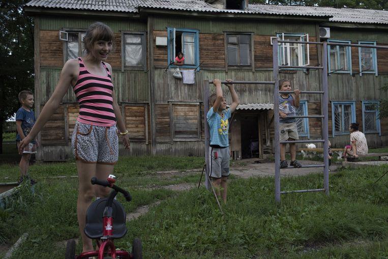 Kinderen spelen voor de barakken die in de jaren twintig door Joodse kolonisten zijn neergezet in Birobidzjan in de speciaal gecreëerde Joodse staat. Beeld Yuri Kozyrev/ Noor Images