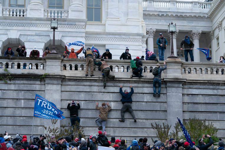 Aanhangers van Donald Trump beklimmen een muur van het Capitool, waar het parlement zetelt en waar de verkiezingszege van Joe Biden zou worden bevestigd. Beeld AP