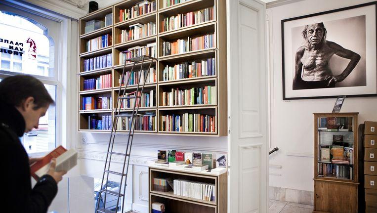 Een boekenliefhebber snuistert in het aanbod van Het Paard van Troje in Leuven. Beeld Bob Van Mol