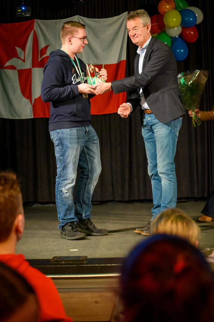 De jeugdige sportman van het jaar Robin van den Hogen krijgt de trofee uit handen van wethouder Rien Wijdeven.