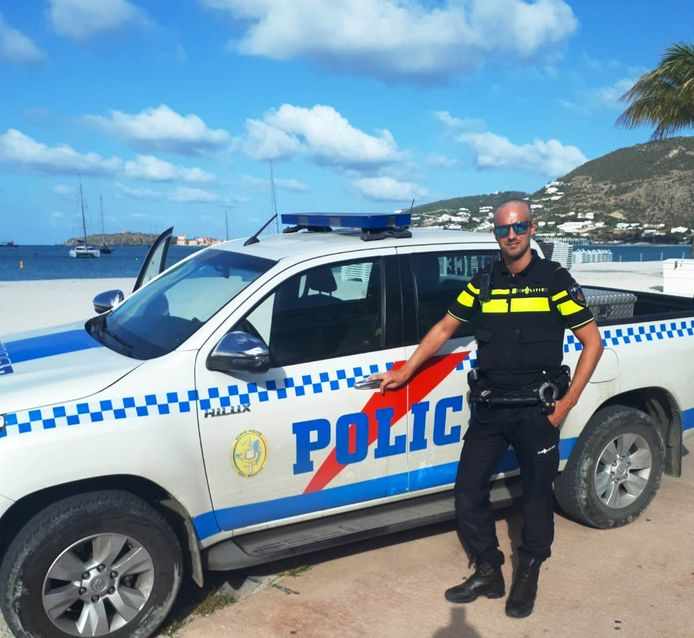 De Steenwijkerlandse hoofdagent Lodewijk ten Brinke met een lokaal politievoertuig op Sint Maarten.