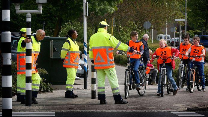 Geen stoplichten, maar verkeersregelaars bepalen of de leerlingen mogen oversteken.