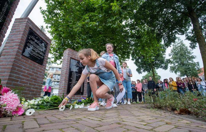 Scholieren leggen bloemen bij het monument aan de Parkweg in Ede.