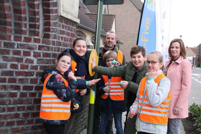 Luna, Miet, Alexis, Henri en Elisa samen met directeur Jeroen Desender van de vrije basisschool Houthulst en mobiliteitsschepen Tessa Vandewalle. De kinderen demonstreren hoe de High-Five werkt