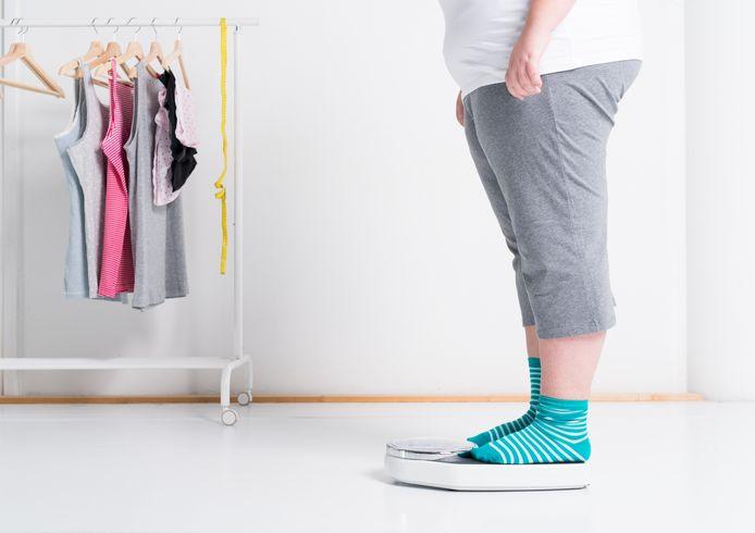 Een vrouw met obesitas op een weegschaal.