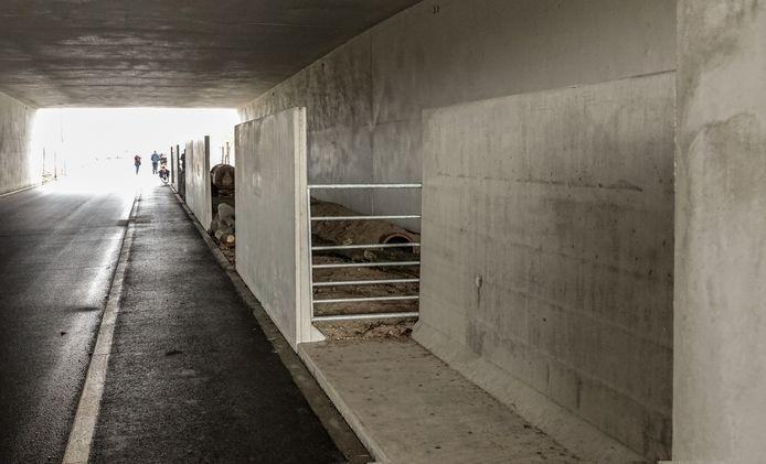 De onverharde strook wordt door muren van de geasfalteerde weg gescheiden.