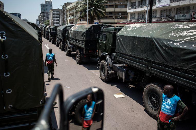 Rijen legertrucks staan geparkeerd in een van de grote straten van Kinshasa. De strijdkrachten hebben onder meer 150 vrachtwagens ter beschikking gesteld om de aanstaande verkiezingen logistiek in goede banen te leiden. Beeld AFP