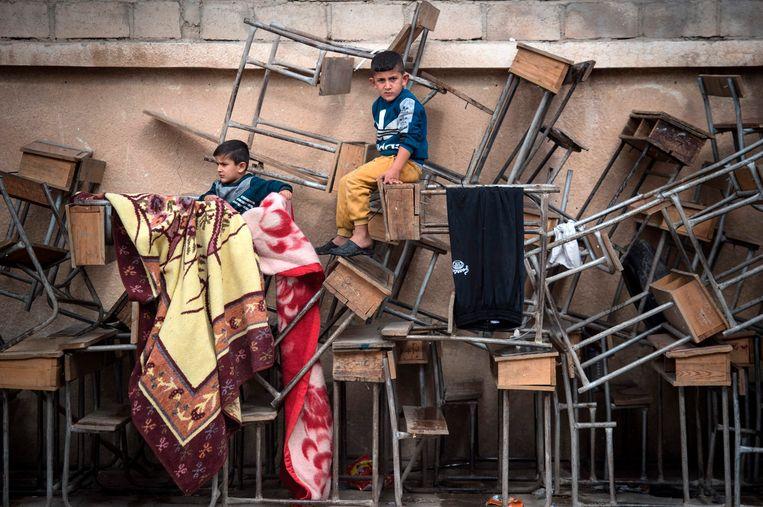 De schoolbanken zijn opzij gezet om in de Syrische stad Hasakeh vluchtelingen op te kunnen vangen. Beeld AFP/FADEL SENNA