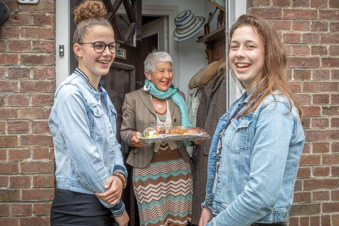 Debora Hoekman en Mathilda Hak verrassen Jeanet Menheere met een ontbijtje.