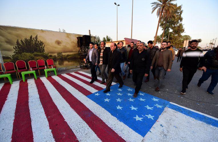 Aanhangers van sjiitische Iraakse milities lopen in Bagdad over een op straat geschilderde Amerikaanse en Israëlische vlag tijdens een rouwprocessie voor enkele van hun medestrijders die omkwamen bij een Amerikaanse aanval eerder deze week.  Beeld EPA