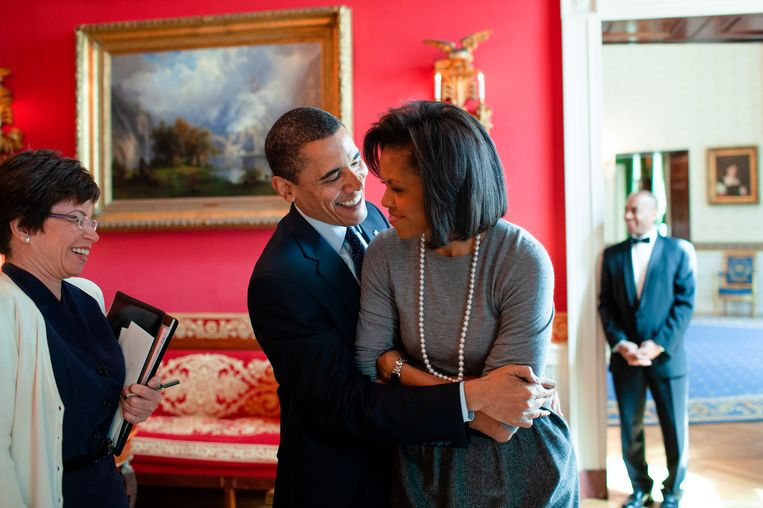 President Barack Obama omhelst first lady Michelle Obama in de Red Room van het Witte Huis, met senior adviseur Valerie Jarrett, 20 maart 2009. Beeld Pete Souza / The White House