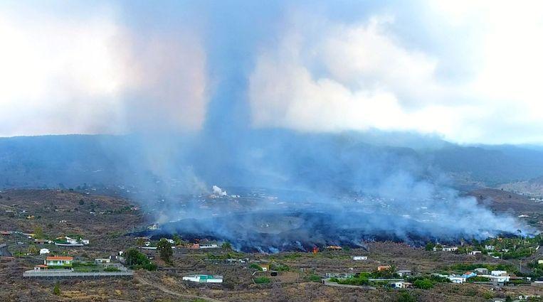 Rook stijgt op vanuit afkoelend lava vlak bij Los Llanos de Aridane op La Palma. Als het hete lava van zo'n 1000 graden de koele zee bereikt, ontstaan mogelijk explosies en komen giftige gassen vrij. Beeld AFP